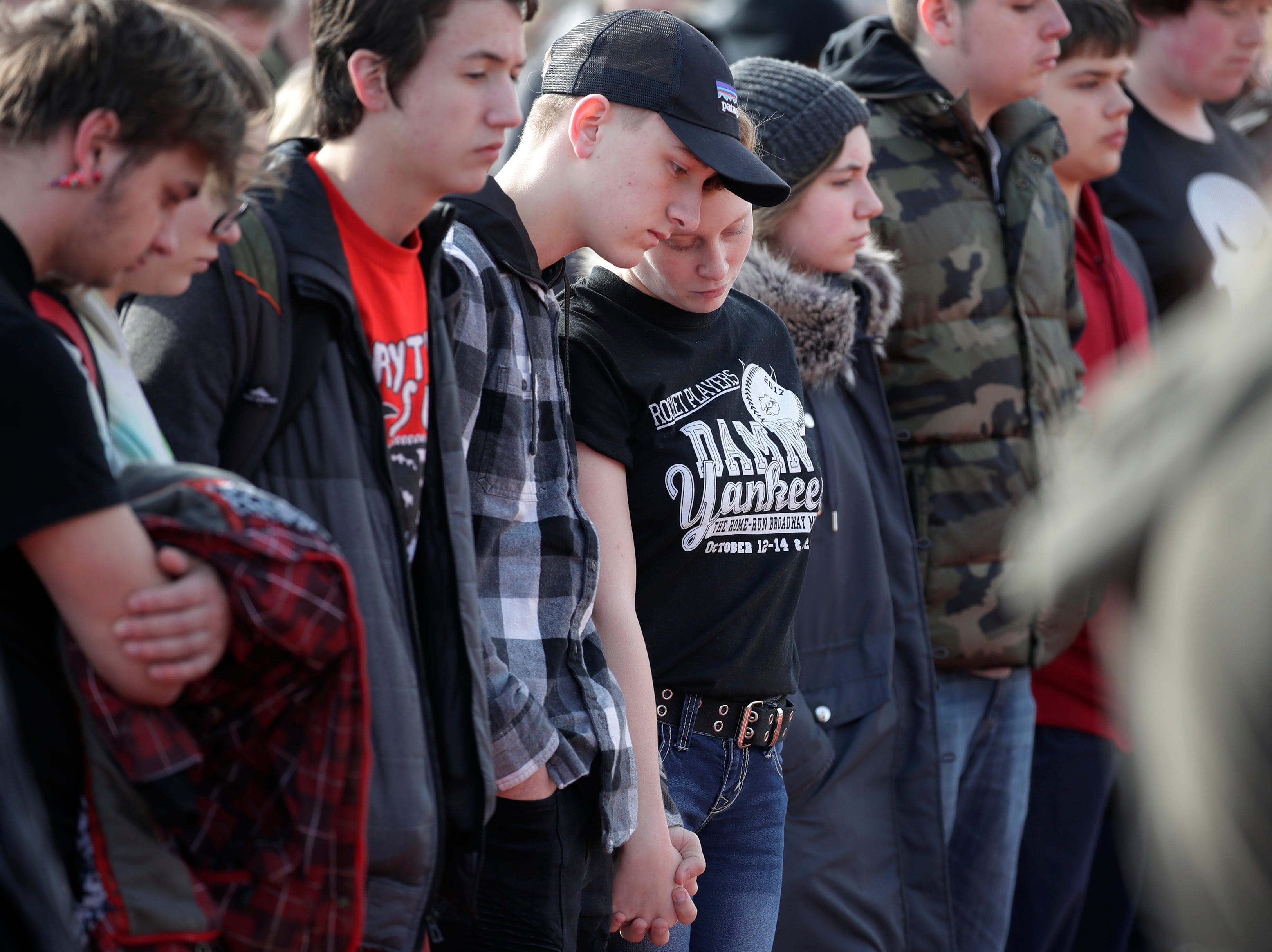 Jackson Blank, a sophomore at Neenah High School, and Brenna Lane, a freshman, hold hands while the names of victims from Marjory Stoneman Douglas High School are read aloud each minute for 17 minutes during National School Walkout Day at Neenah High School Wednesday, March 14, 2018, in Neenah, Wis. 