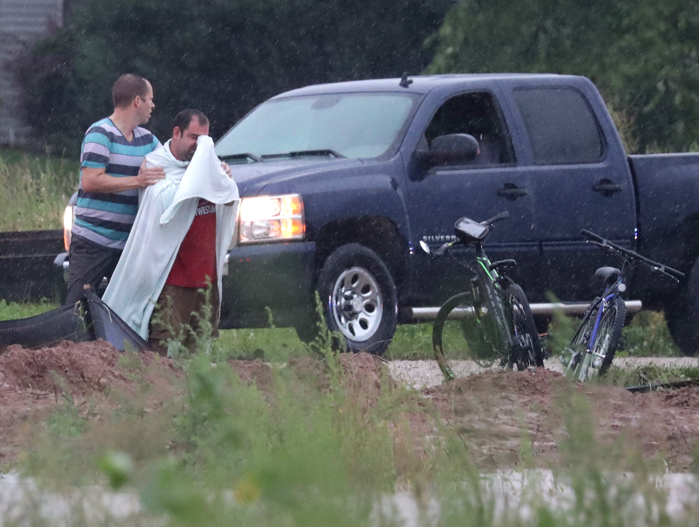 The father of a missing child waits  as Emergency responders, police and firefighters search for the 11 year old boy who dissapeared beneath the water of a drainage ditch while playing with friends on Tuesday, August 28, 2018, in Harrison, Wis. The boy was found, alive, in an air pocket beneath a manhole cover about thirty feet from the place he went missing.