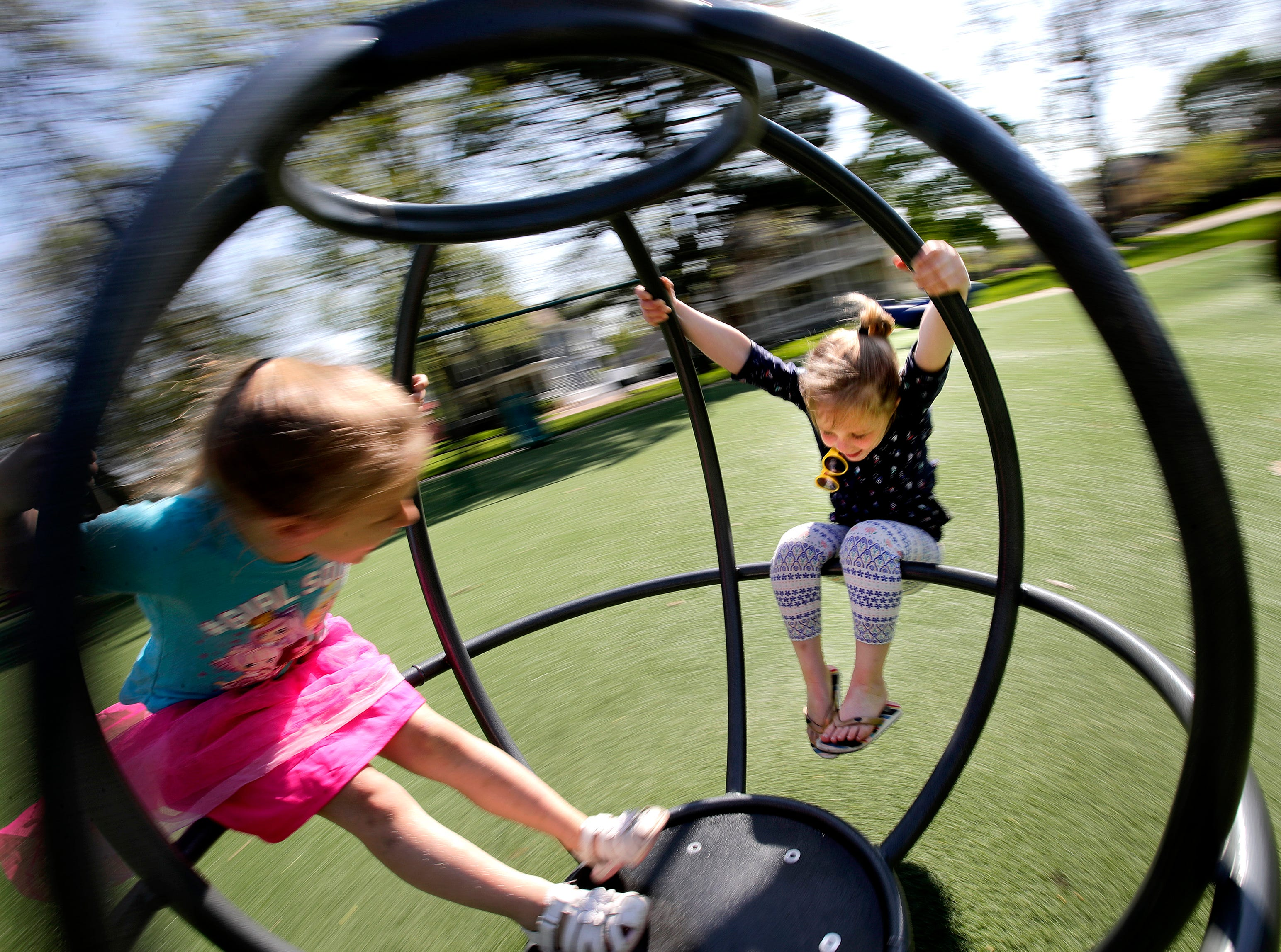 Lydia Probst, 4, spins on the city park merry-go-round with her best friend Mary-Anne Milis, 4, Tuesday, May 15, 2018, in Appleton, Wis. 