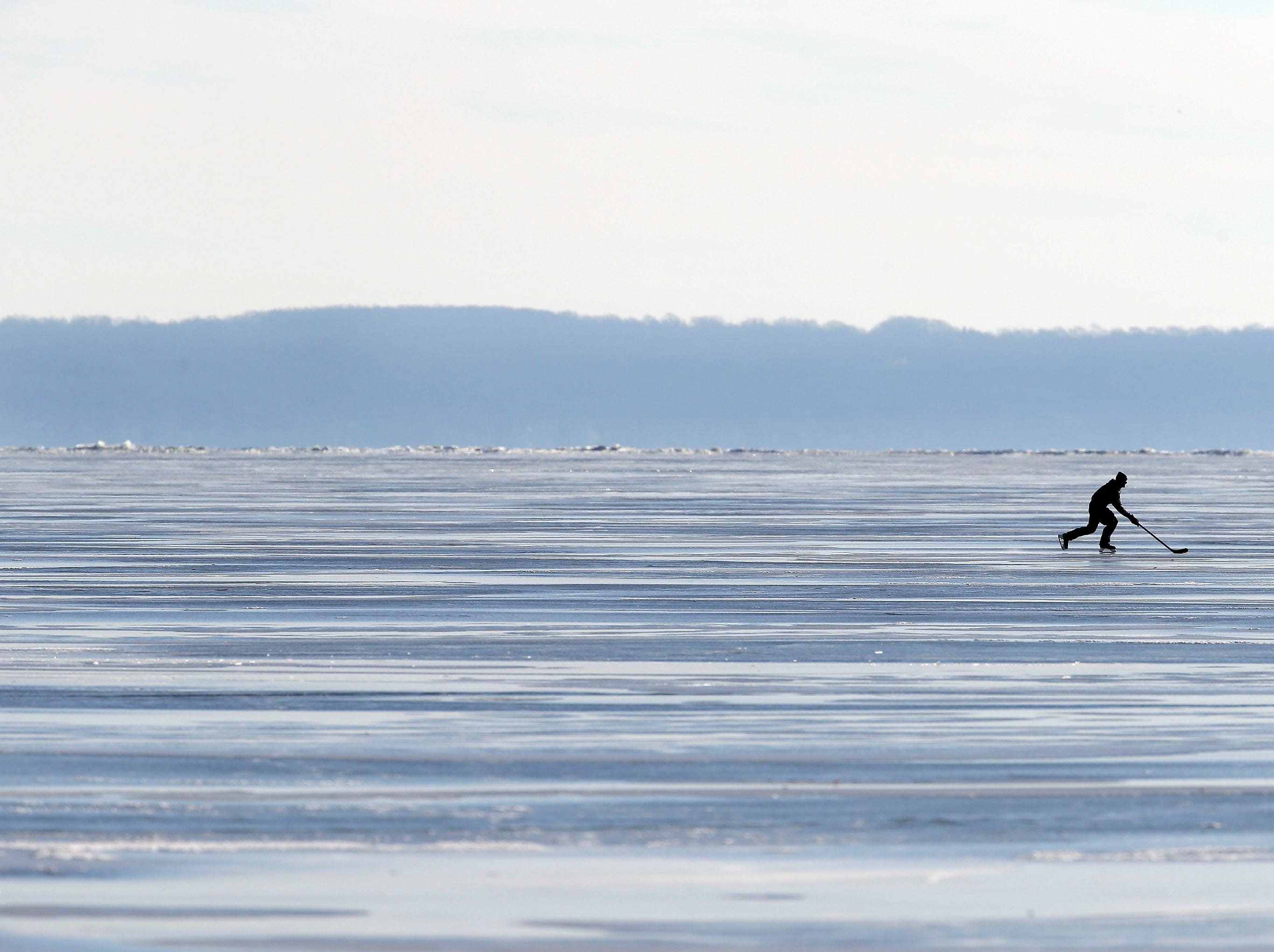 Enterprising or feature hunting is often where we find the images that offer a respite from the hard side of news. I was doing just that on a Sunday and came across a couple of hockey fans on the big lake. One of them broke away and skated on their own for a bit and offered an image of a winter's day in Wisconsin.