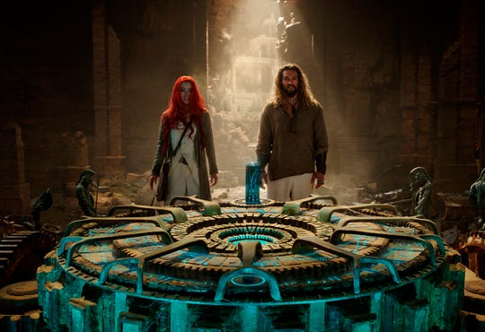 "Amber Heard, left, and Jason Momoa in a scene from ""Aquaman."""