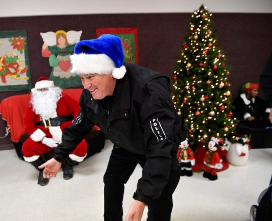 Tye Police Chief Jay Strong bends down to greet a child in the city's community center after a Christmas parade Dec. 20.