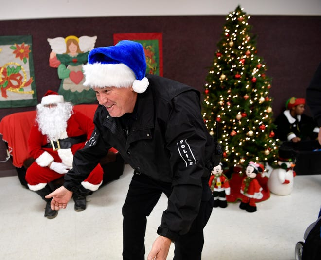 Tye Police Chief Jay Strong bends down to greet a child in the city's community center after Thursday's Christmas parade.