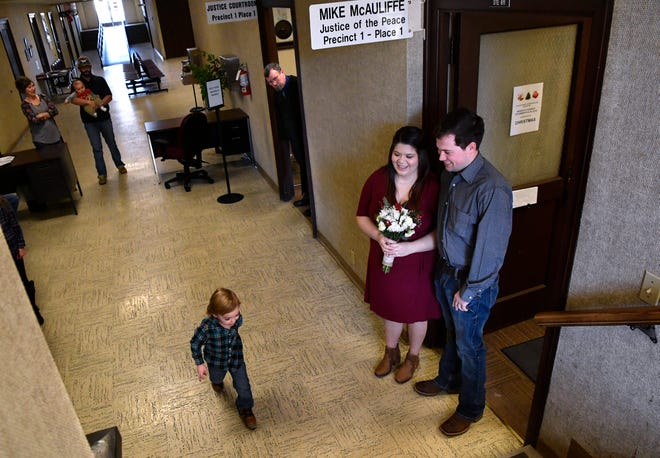 Taylor County Justice of the Peace Mike McAuliffe looks out of his courtroom door to invite Shayle Swink and Eli Martin inside. The young couple were married Friday in the old Taylor County courthouse, which is being considered for renovation.