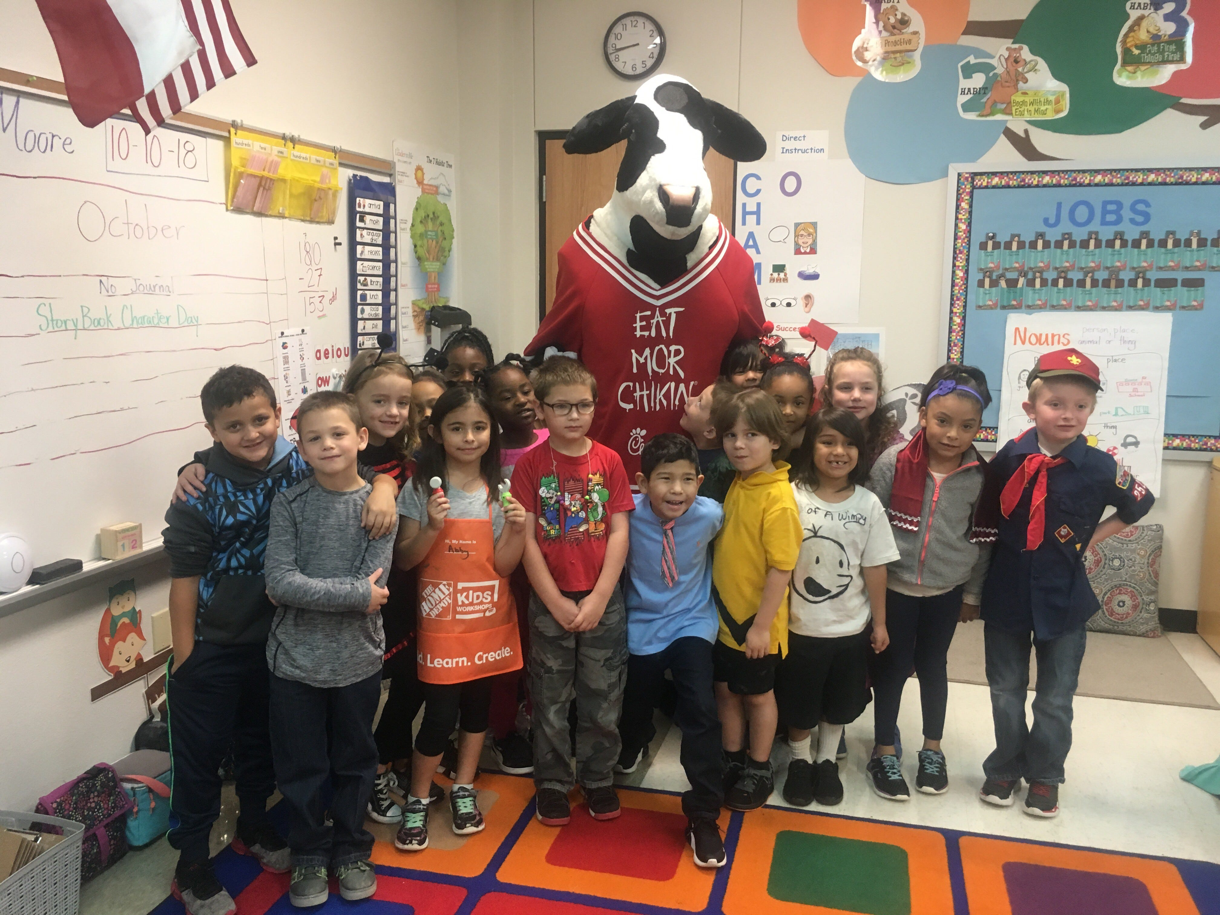"""The Chick-fil-A mascot visits Mary Jane Moore's first grade class at Bowie Elementary School for the Altrusa International of Abilene """"Reading Rodeo."""""""