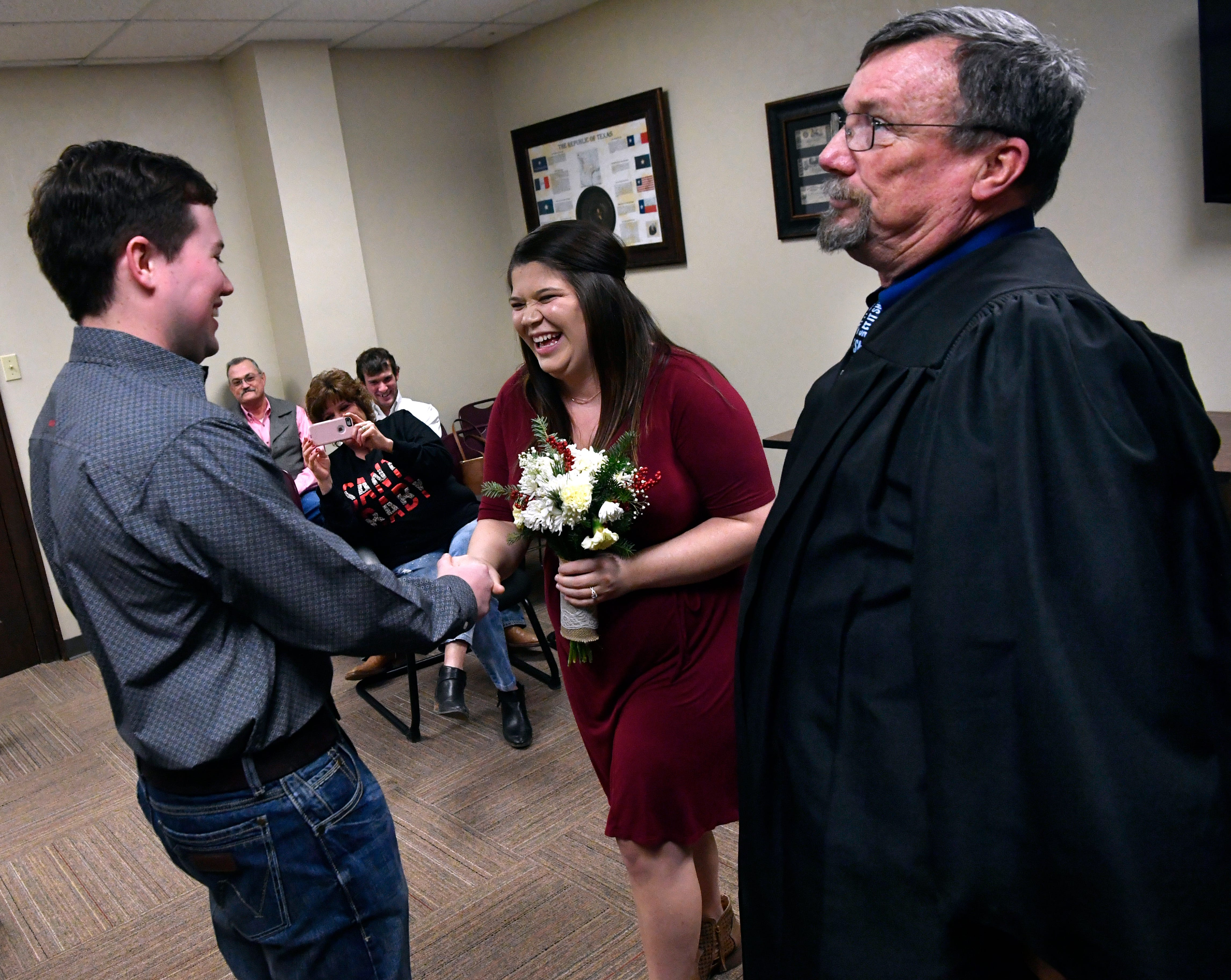 Taylor County Justice of the Peace Mike McAuliffe teases soon-to-be-newlyweds Eli Martin and Shayle Swink during their ceremony Friday in the basement courtroom of the former Taylor County courthouse. The 103-year-old building is being considered for renovation.