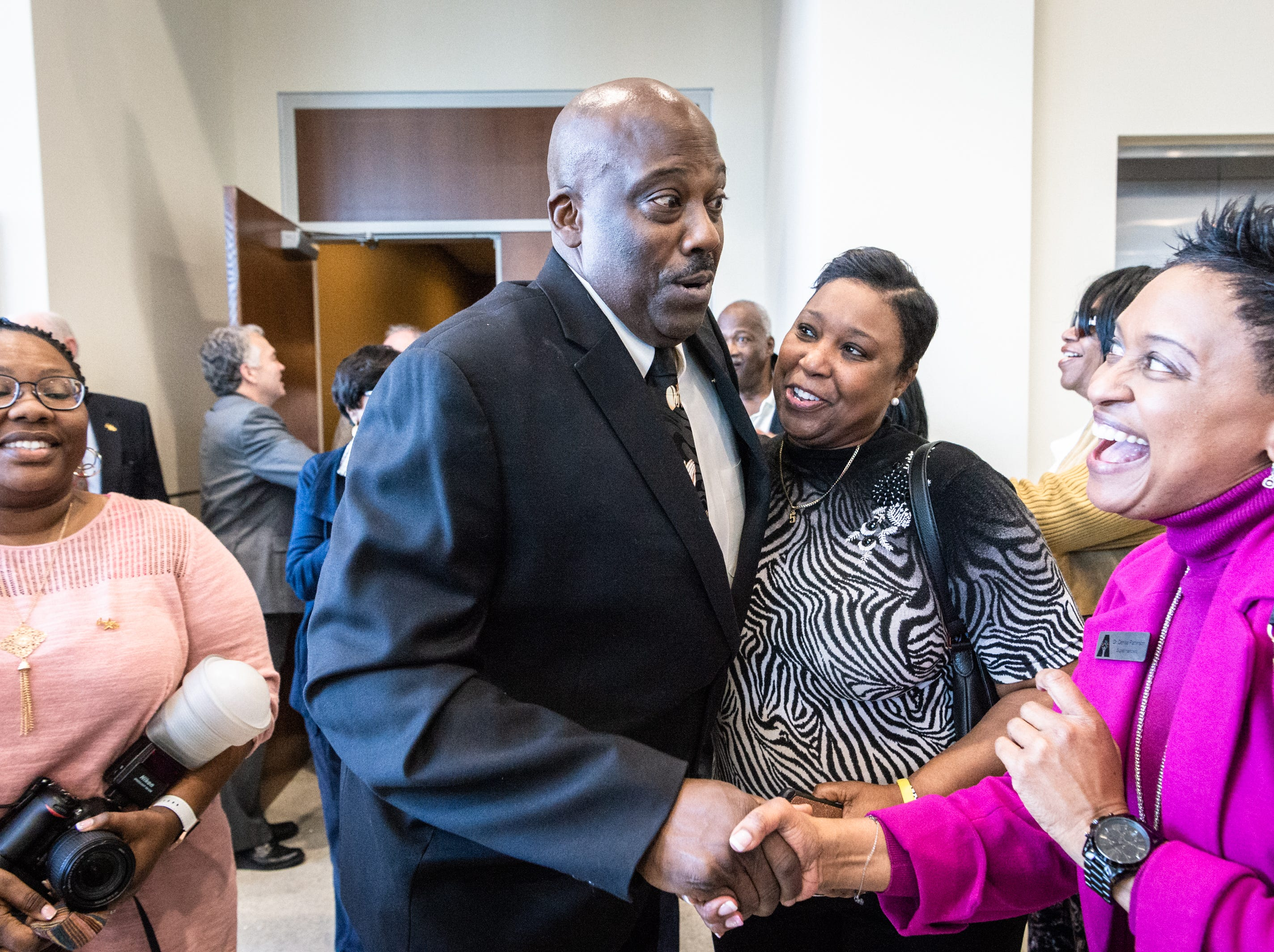 Quentin Miller, the new Buncombe County Sheriff greets friends, family and supporters after leaving the courtroom at the Buncombe County Courthouse after his swearing-in ceremony Dec. 3, 2018, making him the first African-American Buncombe County sheriff.