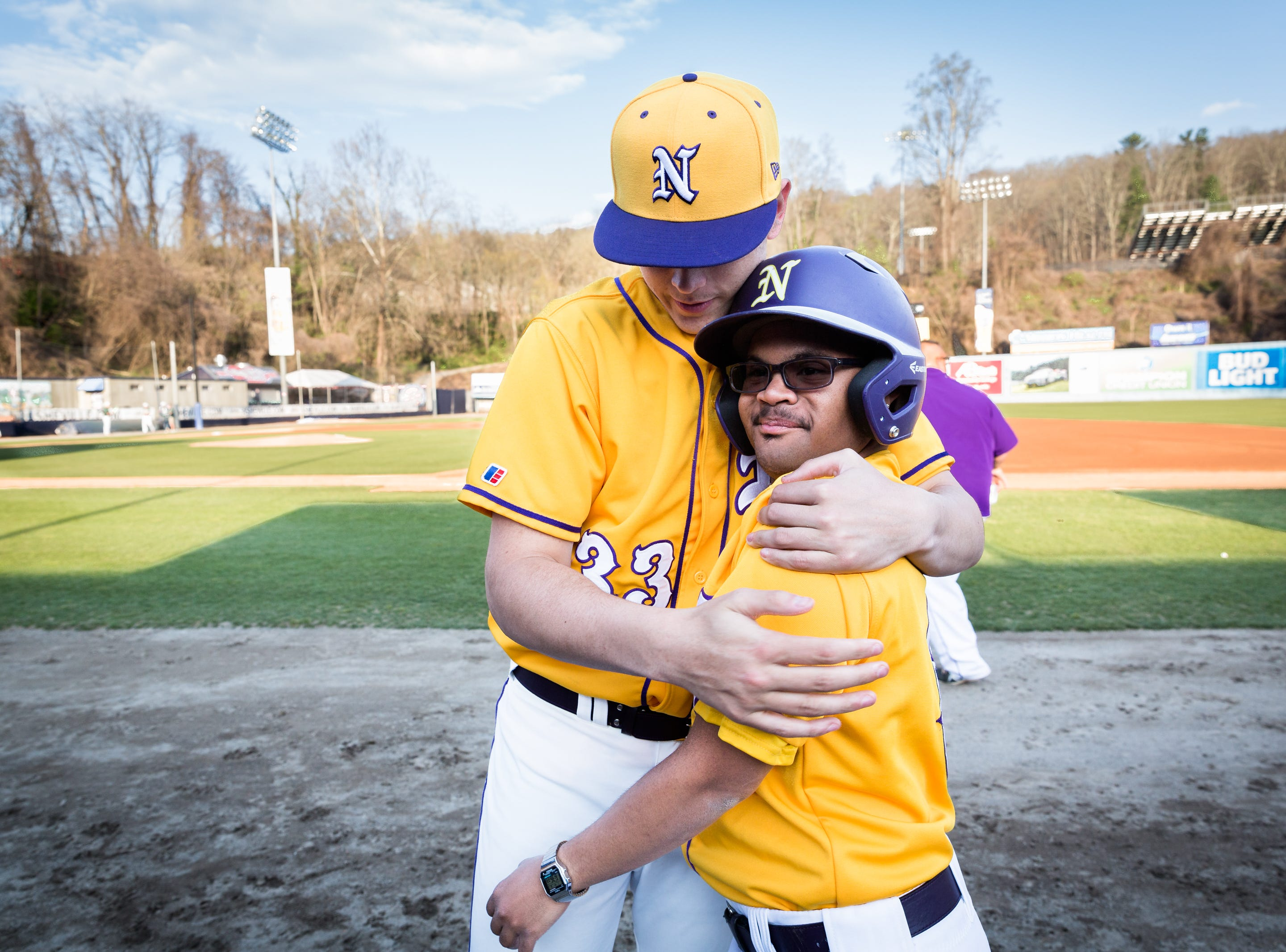 North Henderson's Gabe Murphy embraces teammate and assistant coach Alex Suder before their game against East Henderson at McCormick Field in Asheville Tuesday, April 4, 2018.