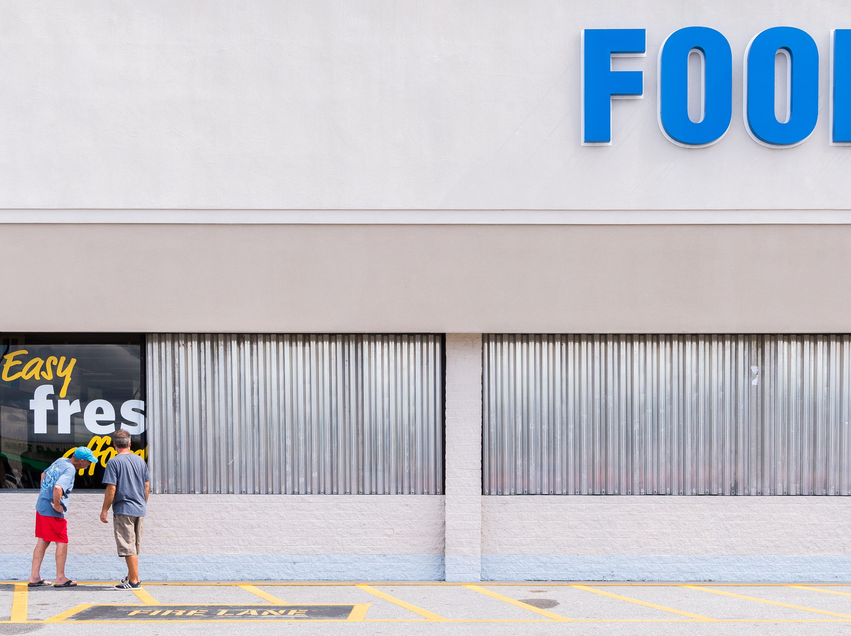 A couple customers at Food Lion in Belhaven inspect the metal sheets placed over the front windows before Hurricane Florence makes landfall, Sept. 12, 2018. A storm surge of about three to six feet is expected for Swan Quarter, and around six feet for Ocracoke Island with 12-20 inches of rainfall for the entire area. Hyde county as well as several surrounding counties are under mandatory evacuation.