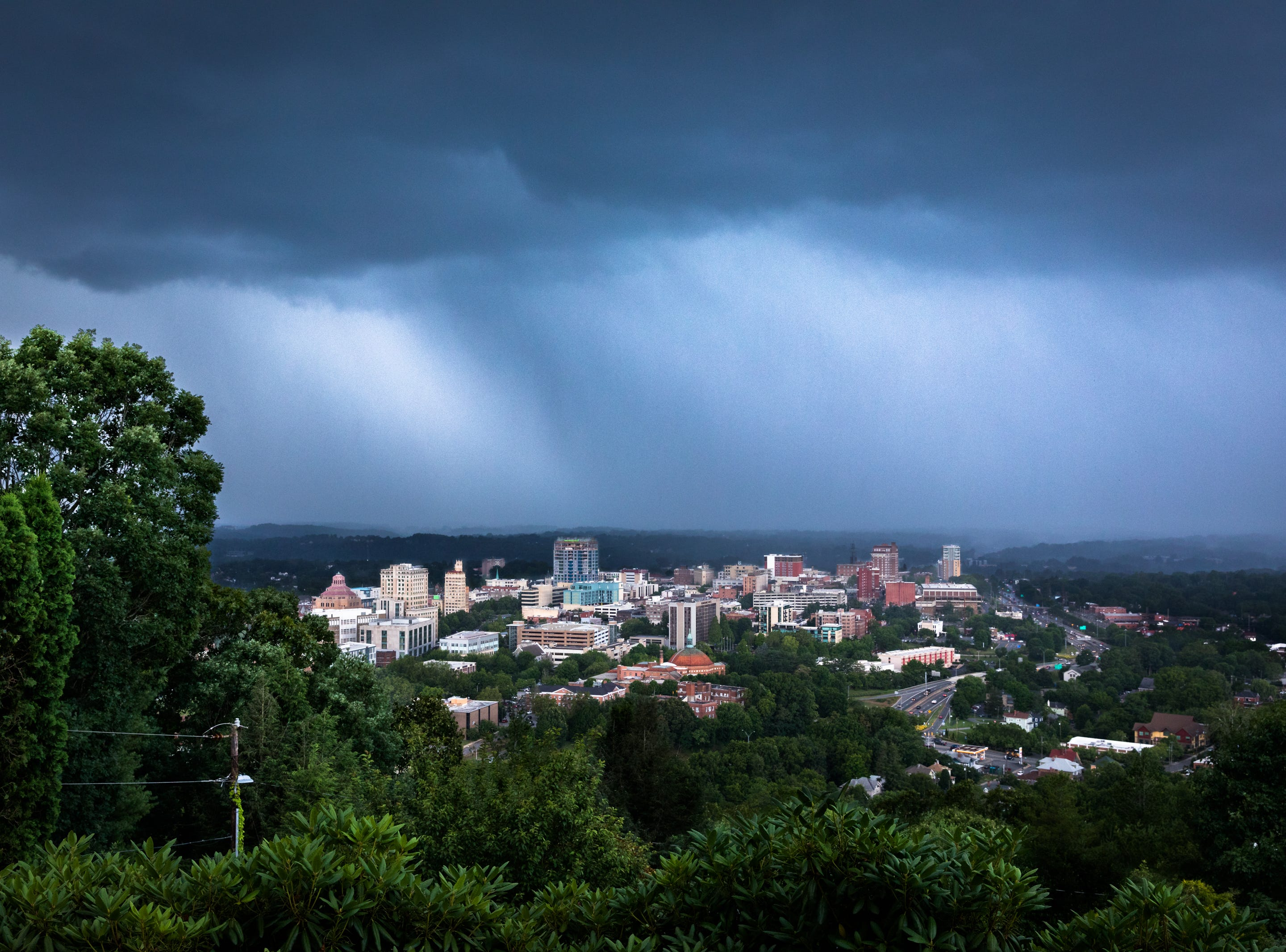 Heavy rain moves in over downtown Asheville as seen from Town Mountain Road Jun. 26, 2018.