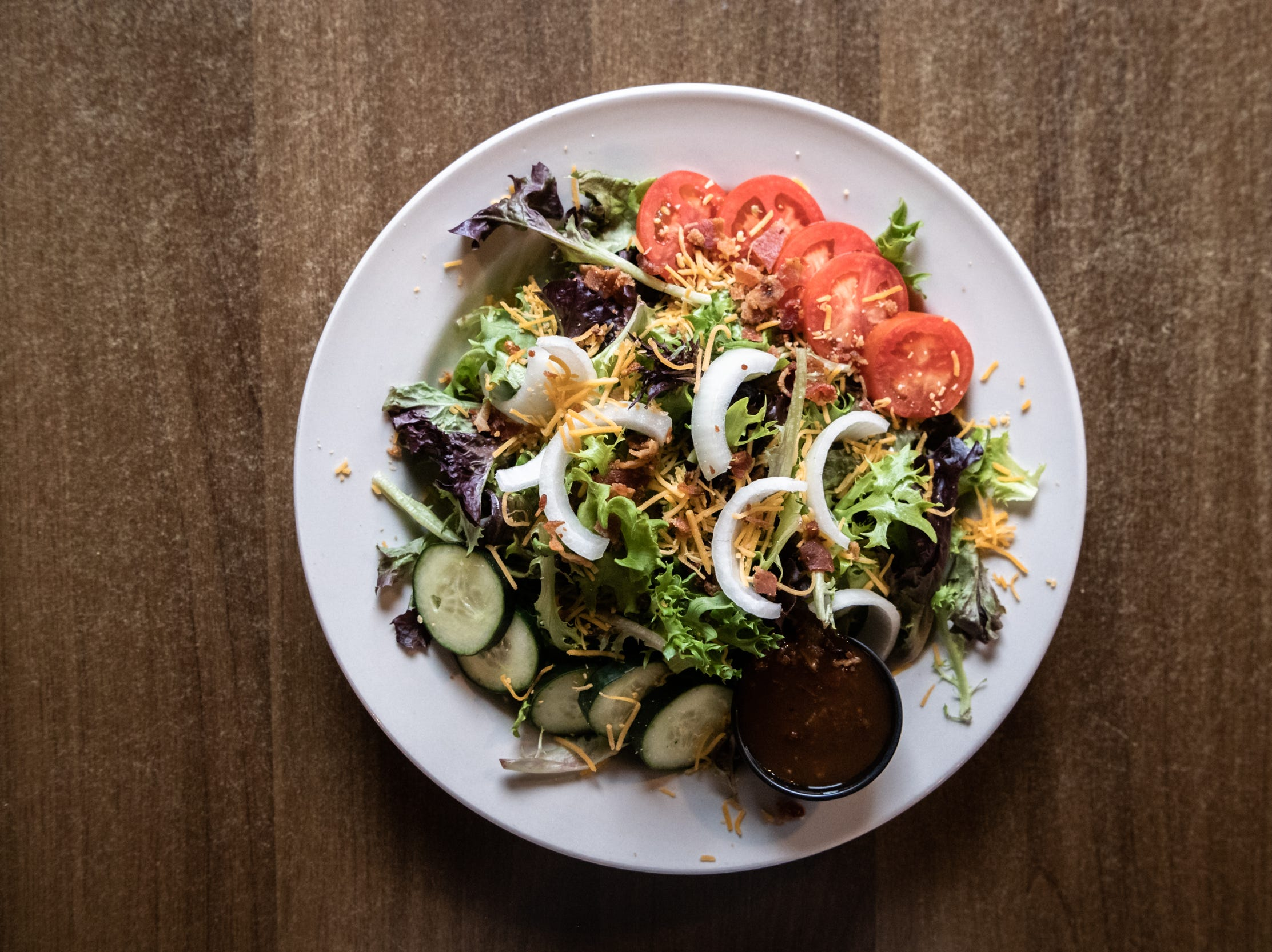 The Southern Porch salad with spring mix, tomatoes, cucumbers, onions, bacon bits, cheese and Southern Porch house dressing, offered at Southern Porch restaurant in Canton.
