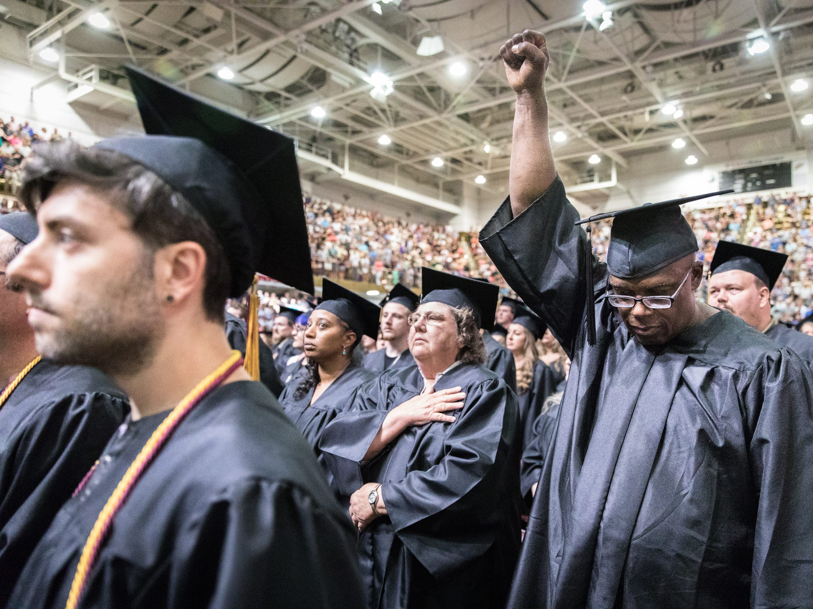Idris Salaam, a prospective graduate of A-B Tech's hospitality management and culinary arts programs, raises his fist during the singing of the national anthem at their commencement at the U.S Cellular Center Saturday, May 12, 2018