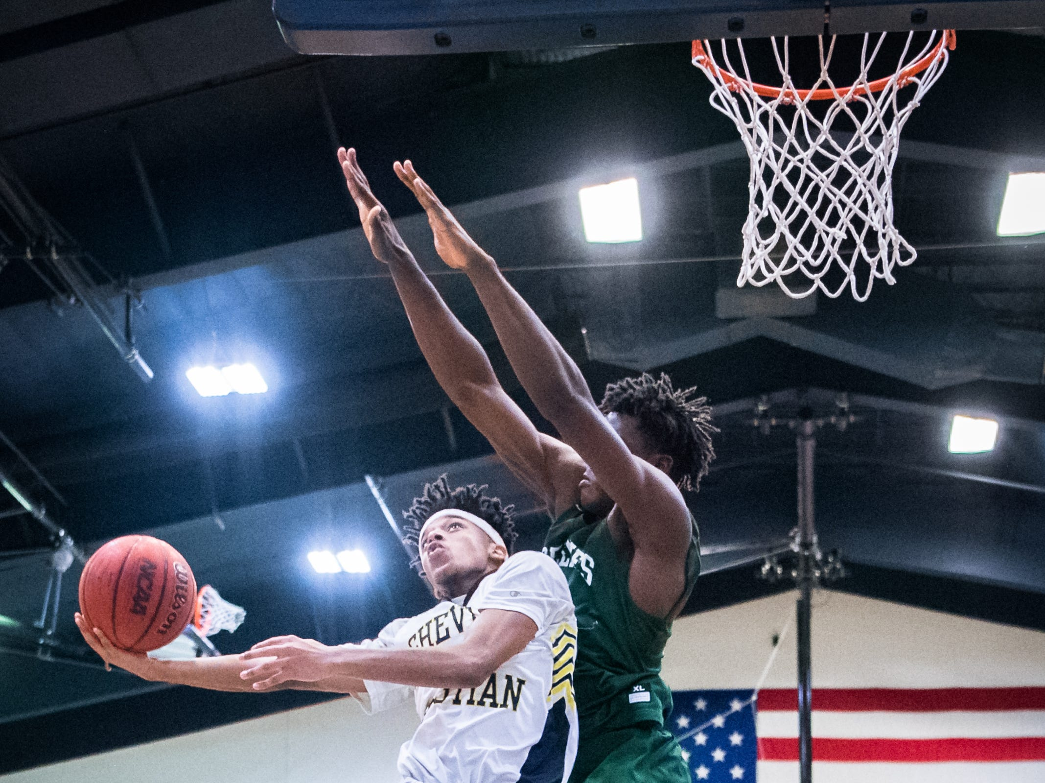 Asheville Christian Academy's Raishaun Brown jumps up for a shot guarded by Christ School's Justice Ajogbor during their game Tuesday, January 9, 2018.