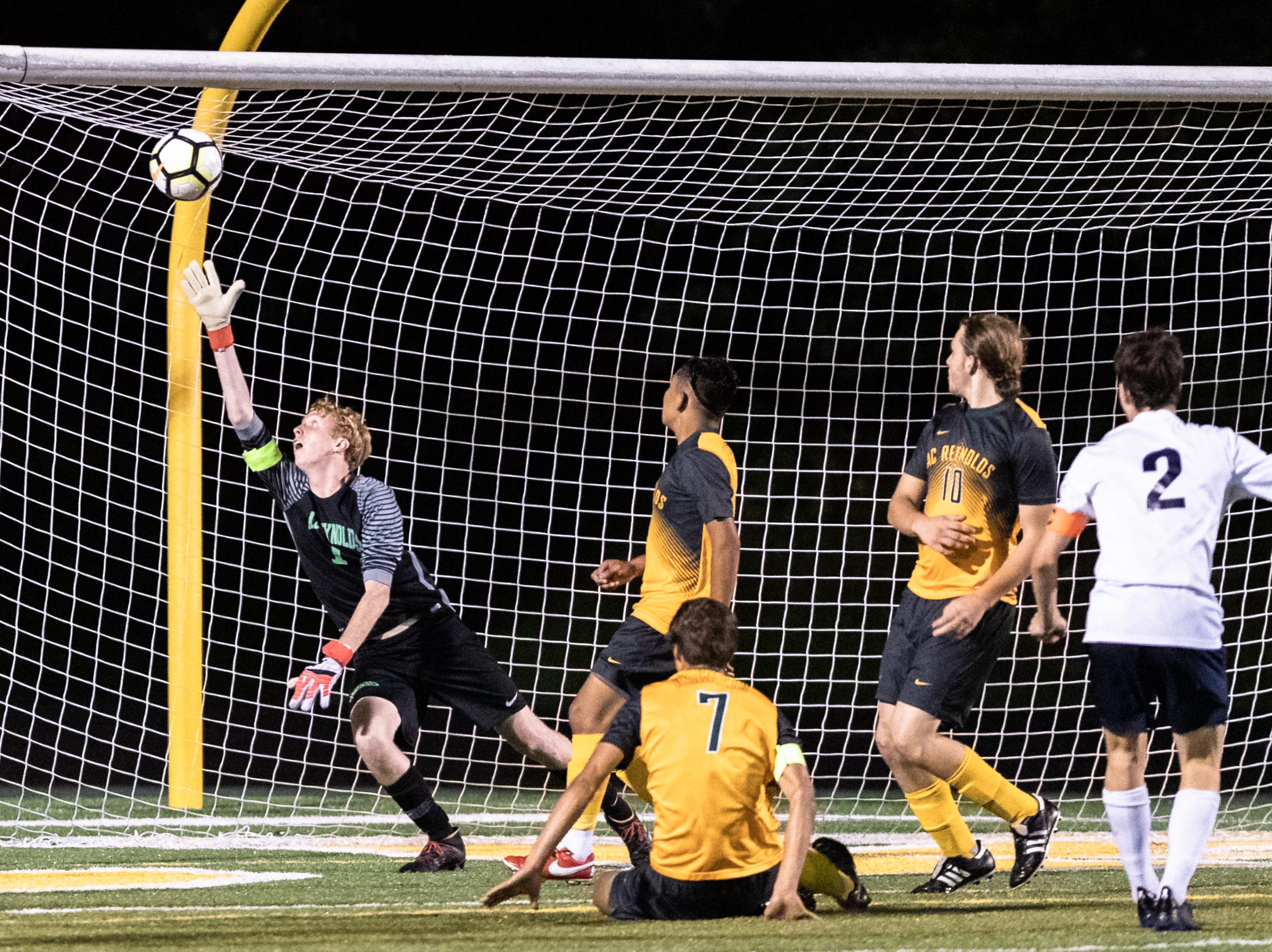Roberson's Henry Asbill gets a shot past Reynolds' goalkeeper Alec Stacey during their game Sept. 24, 2018. Reynolds won 2-1.