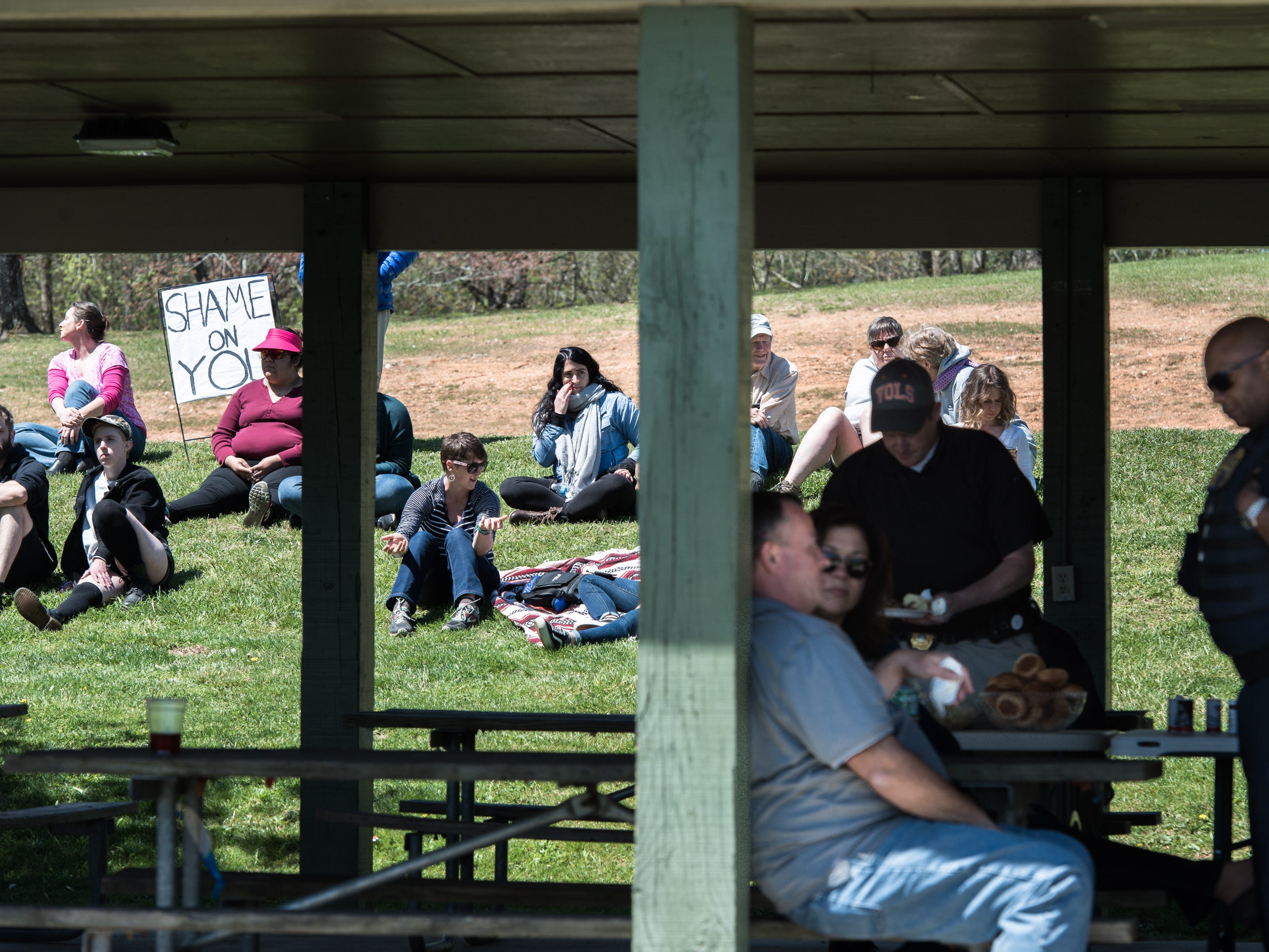 People gather with signs at Jackson Park in Hendersonville to protest where ICE, Homeland Security and other local law enforcement agents gathered for a picnic Friday, April 20, 2018.