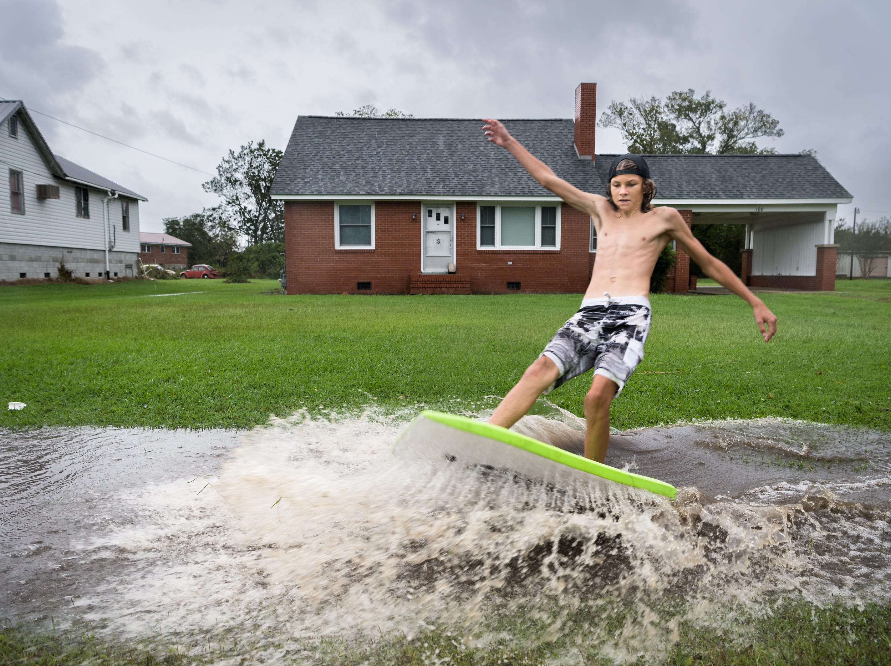 Deacon Etheridge, 14, surfs on a large puddle on Main Street in Swan Quarter, N.C Sept. 14, 2018, after Hurricane Florence made landfall.