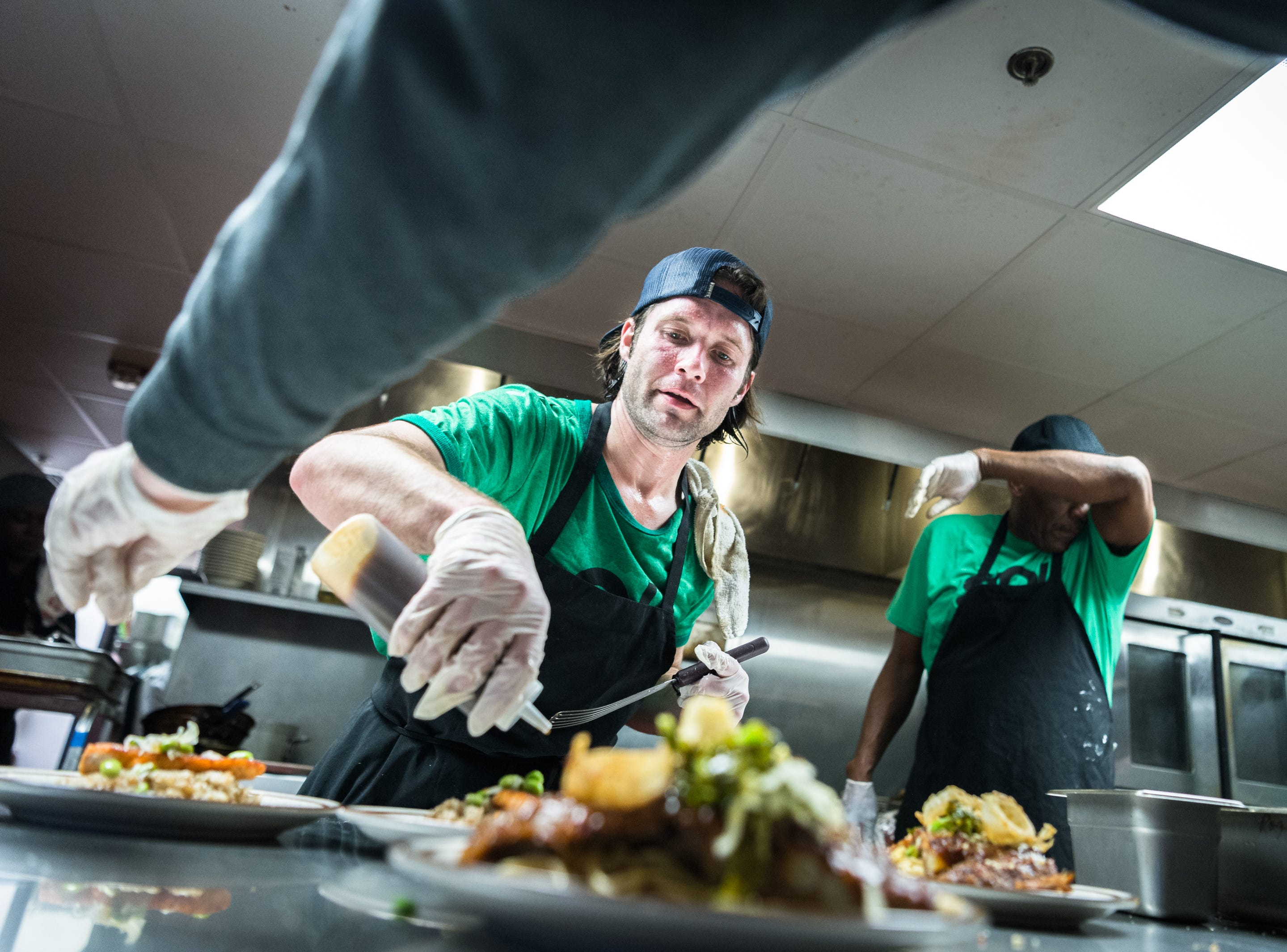 Daniel Burroughs, a student in Green Opportunities' Kitchen Ready program plates food during their showcase dinner at the Southside Kitchen in Asheville Thursday, February 22, 2018.