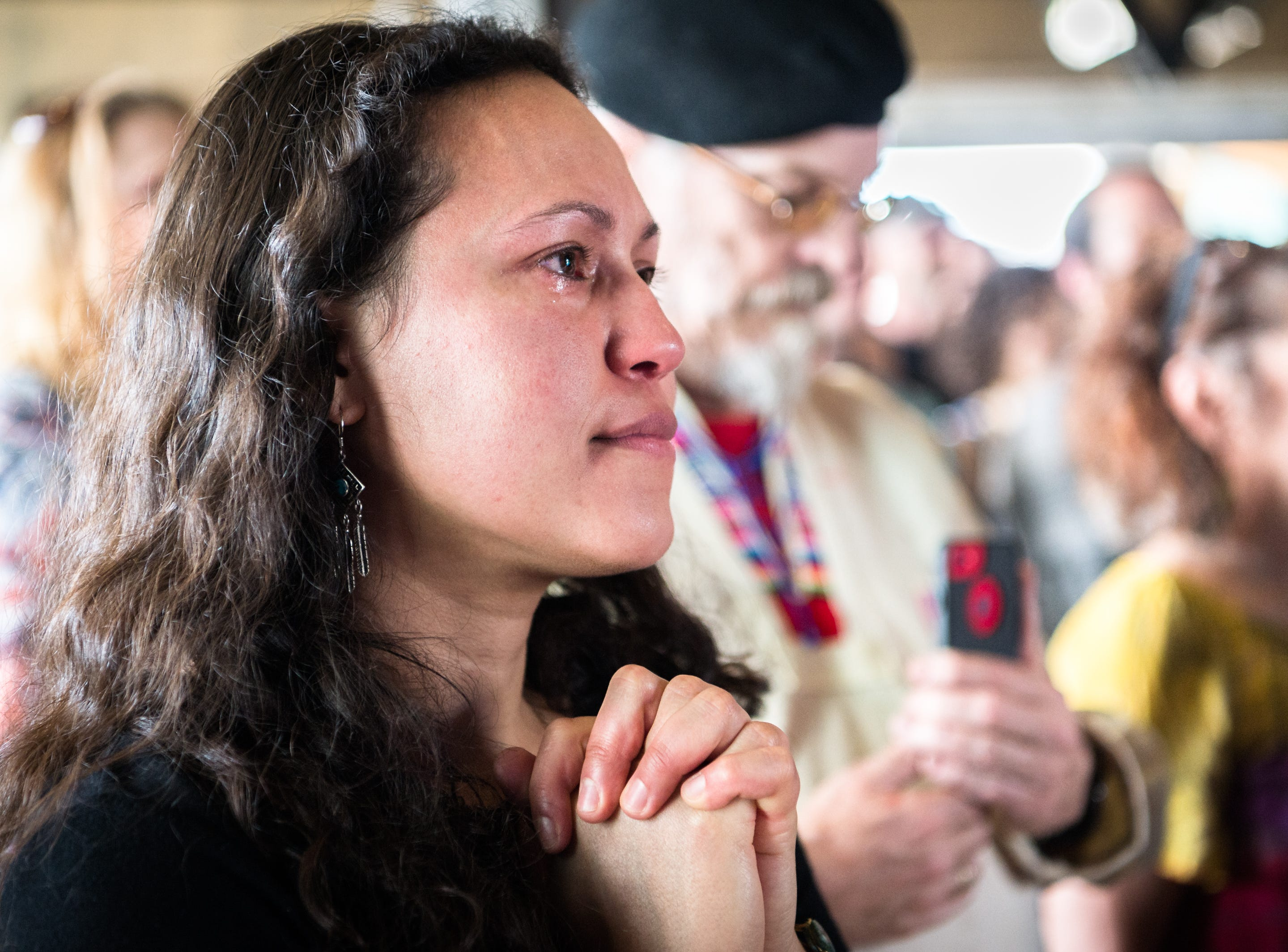 Mari Echevarria, a friend of Tyler Garrison, founder of Junk Recyclers, and The Regeneration Station, listens to friends and loved ones speak at Salvage Station at a celebration of his life after he was killed in a motorcycle accident in Dallas on Sunday.