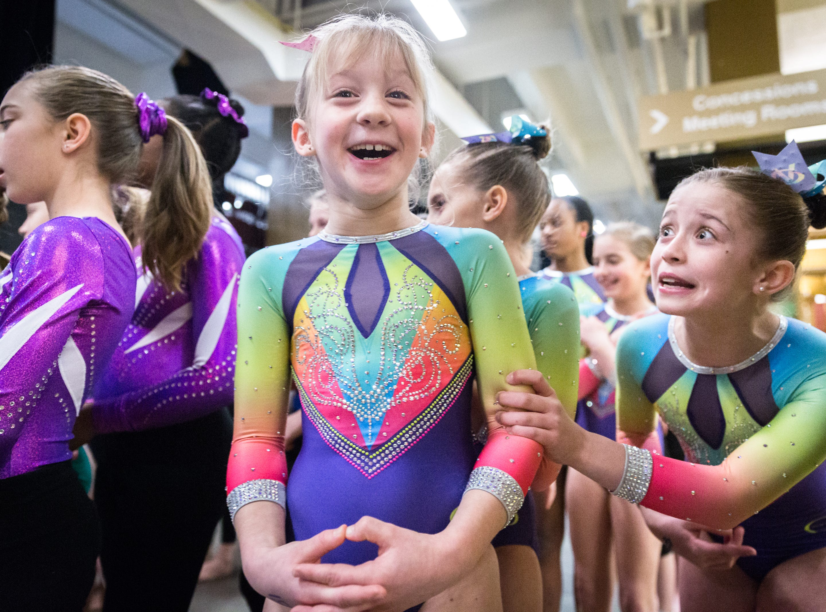 """Payton McNally, 10, of Premiere Athletics based in Knoxville, Tennessee, grabs the arm of teammate Lily Hughes, 9, asking her, """"are you scared?"""" before their team is announced and escorted onto the floor before competition begins at the Gymnastics Gala meet at the U.S Cellular Center in Asheville, Saturday, January 6, 2017. Teams came from Florida, Georgia, North Carolina, South Carolina, and Tennessee."""
