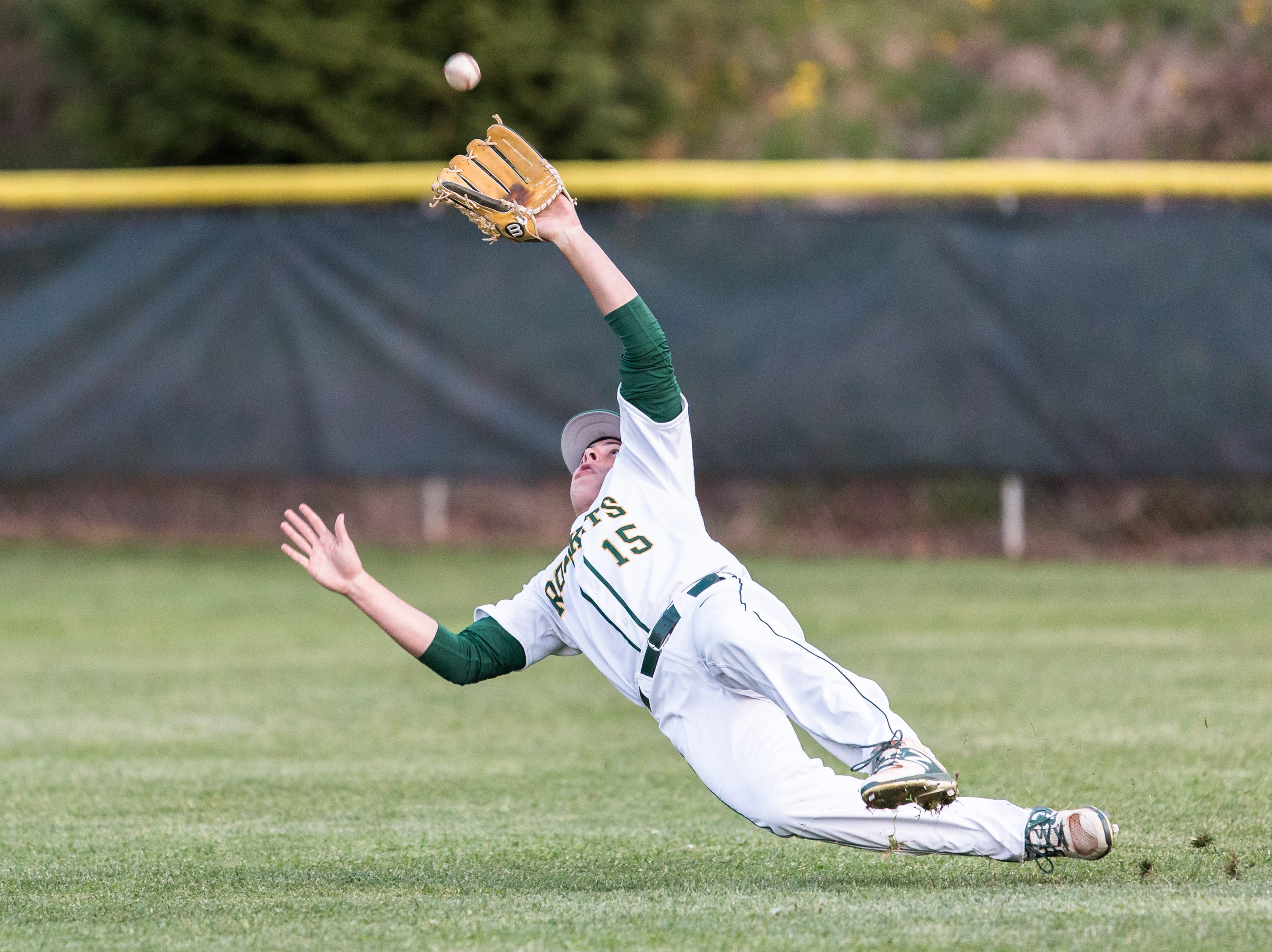 Reynolds' Alex Flinn dives to make a catch in the outfield for an out during their game against North Buncombe Friday, April 20, 2018.