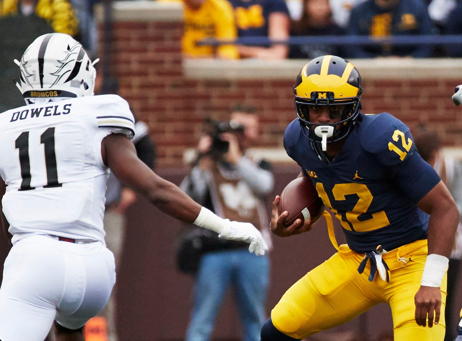Sep 8, 2018; Ann Arbor, MI, USA; Michigan Wolverines running back Chris Evans (12) runs the ball against Western Michigan Broncos defensive back Juwan Dowels (11) in the first half at Michigan Stadium. Mandatory Credit: Rick Osentoski-USA TODAY Sports