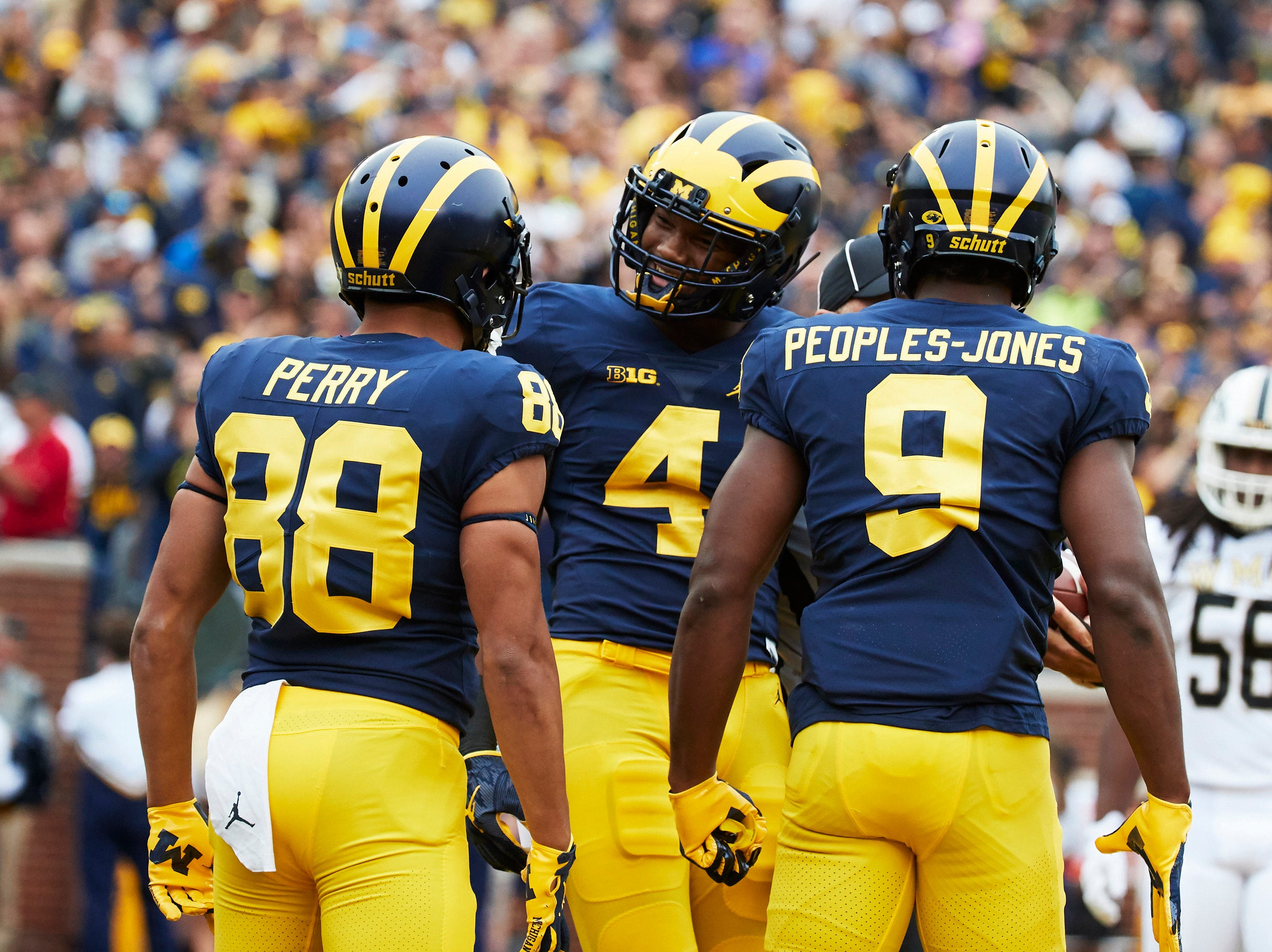 Sep 8, 2018; Ann Arbor, MI, USA; Michigan Wolverines wide receiver Nico Collins (4) is congratulated by wide receiver Grant Perry (88) and wide receiver Donovan Peoples-Jones (9)  after scoring a touchdown against the Western Michigan Broncos in the first half at Michigan Stadium. Mandatory Credit: Rick Osentoski-USA TODAY Sports
