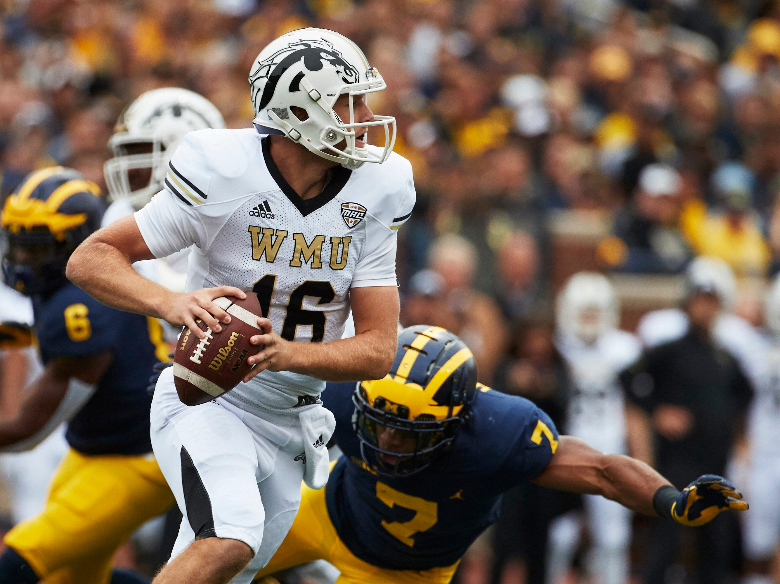 Sep 8, 2018; Ann Arbor, MI, USA; Western Michigan Broncos quarterback Jon Wassink (16) scrambles on Michigan Wolverines linebacker Khaleke Hudson (7) in the first half at Michigan Stadium. Mandatory Credit: Rick Osentoski-USA TODAY Sports