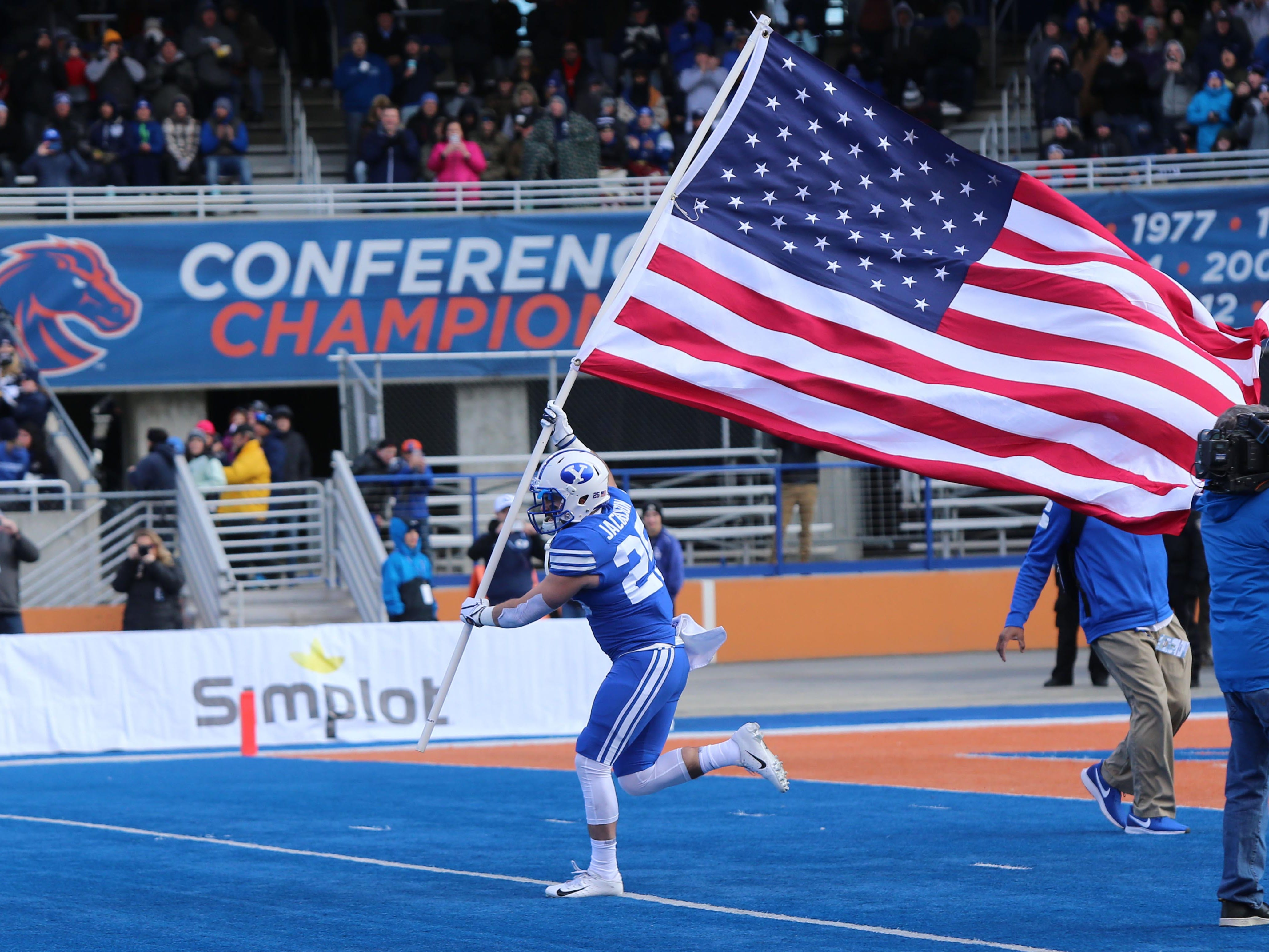 Dec 21, 2018; Boise, ID, United States; Brigham Young Cougars running back Tanner Jacobson (25) carries the American flag onto the field prior to the first half  of play versus the Western Michigan Broncos at the 2018 Potato Bowl at Albertsons Stadium. Mandatory Credit: Brian Losness-USA TODAY Sports