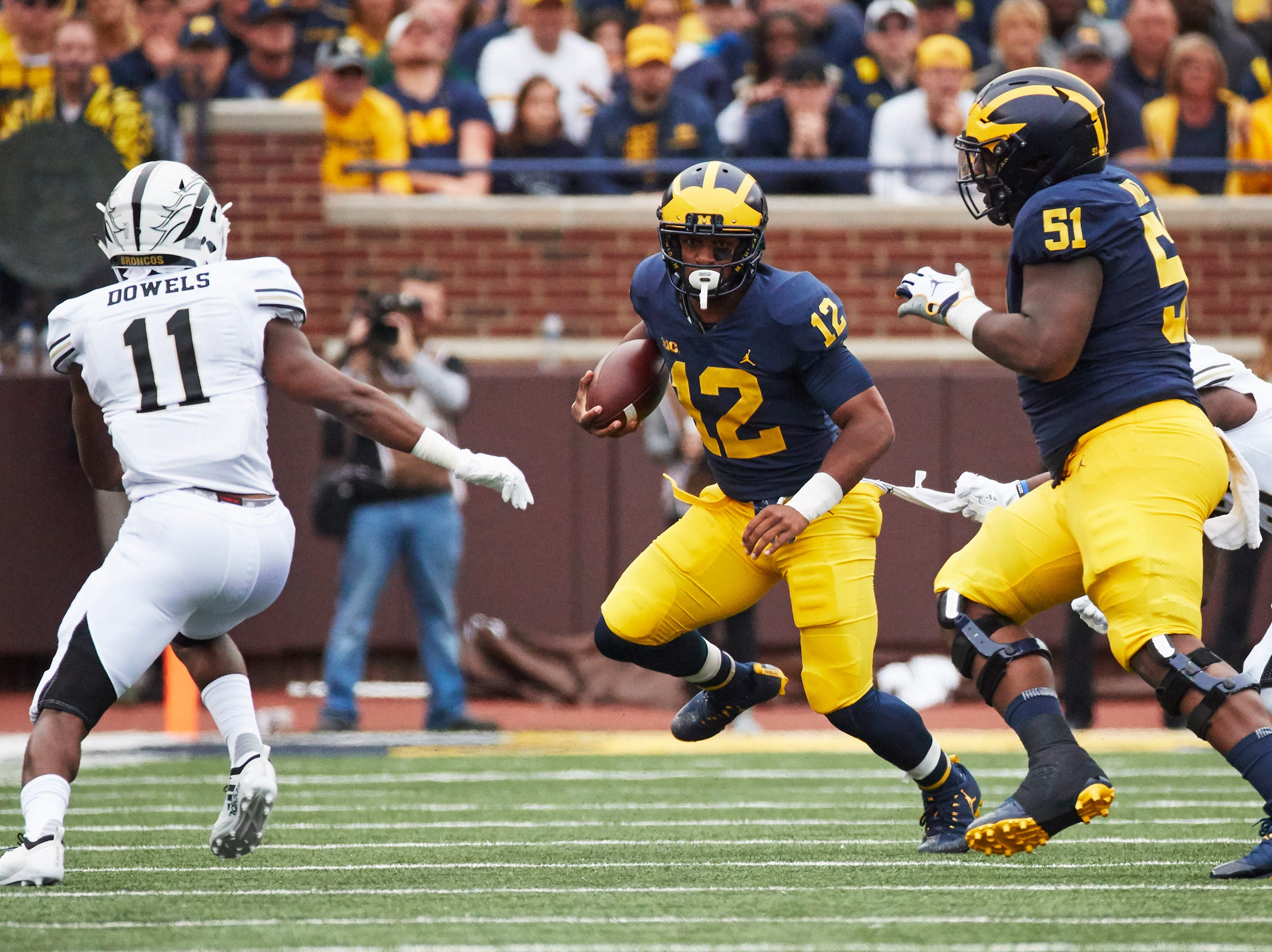 Sep 8, 2018; Ann Arbor, MI, USA; Michigan Wolverines running back Chris Evans (12) runs the bases at Western Michigan Broncos defensive back Juwan Dowels (11) in the first half at Michigan Stadium. Mandatory Credit: Rick Osentoski-USA TODAY Sports