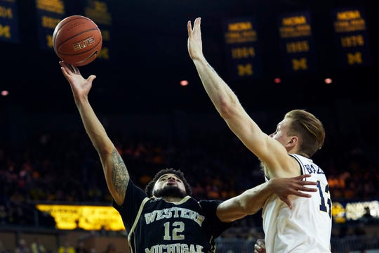 Dec 15, 2018; Ann Arbor, MI, USA; Western Michigan Broncos guard Michael Flowers (12) shoots on Michigan Wolverines forward Ignas Brazdeikis (13) in the second half at Crisler Center. Mandatory Credit: Rick Osentoski-USA TODAY Sports
