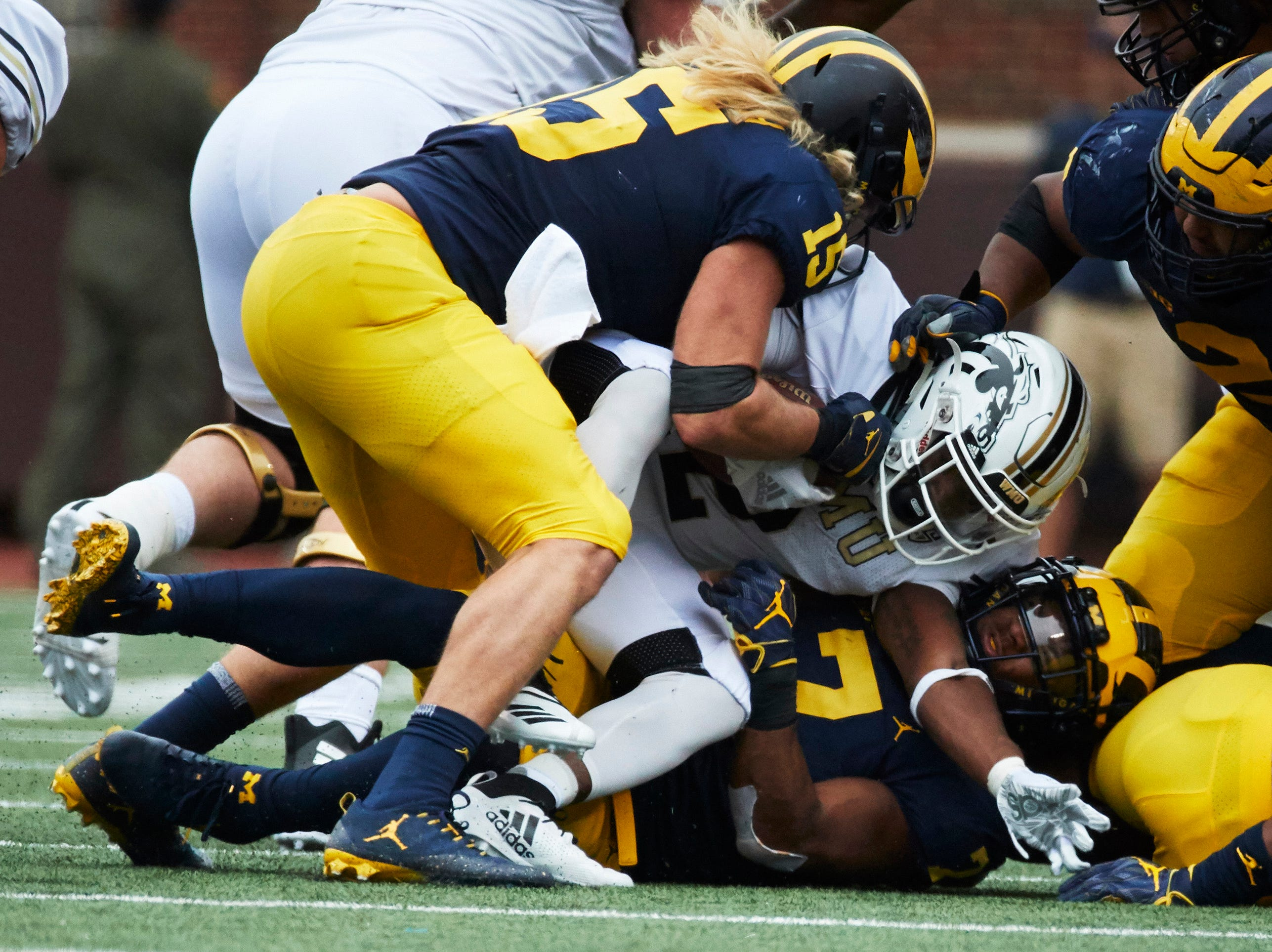 Sep 8, 2018; Ann Arbor, MI, USA; Western Michigan Broncos running back LeVante Bellamy (2) is tackled by Michigan Wolverines defensive lineman Chase Winovich (15) and linebacker Khaleke Hudson (7) in the first half at Michigan Stadium. Mandatory Credit: Rick Osentoski-USA TODAY Sports