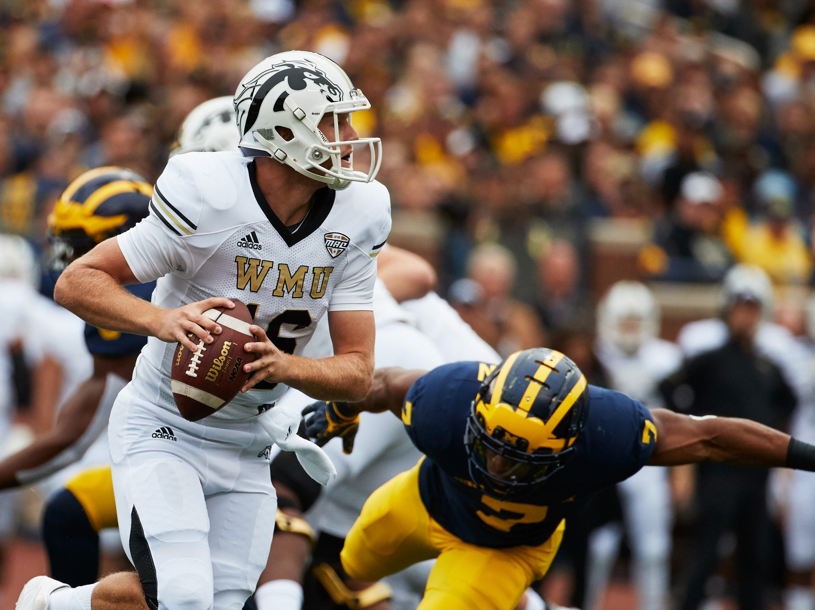 Sep 8, 2018; Ann Arbor, MI, USA; Western Michigan Broncos quarterback Jon Wassink (16) scramble on Michigan Wolverines linebacker Khaleke Hudson (7) in the first half at Michigan Stadium. Mandatory Credit: Rick Osentoski-USA TODAY Sports