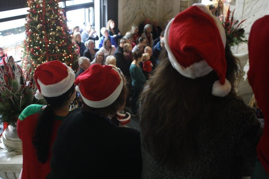 Security Mutual employees donned Santa hats and festive attire as they sang Christmas carols in the building's lobby Friday afternoon.