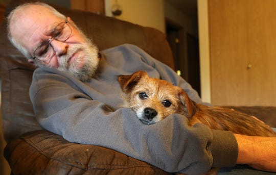 John O'Connor's dog Spanky snuggles in his arms at their Port Orchard home on Thursday, December 20, 2018.