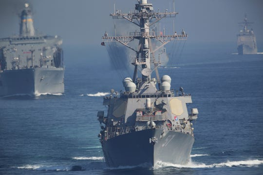 The USS Mitscher, center, and other vessels in a strike group sail behind the USS John C. Stennis aircraft carrier on Friday, Dec. 21, 2018. The U.S. aircraft carrier sailed into the Persian Gulf on Friday, becoming the first since America's withdrawal from the Iran nuclear deal and breaking the longest carrier absence in the volatile region since at least the Sept. 11 terror attacks. (AP Photo/Jon Gambrell)