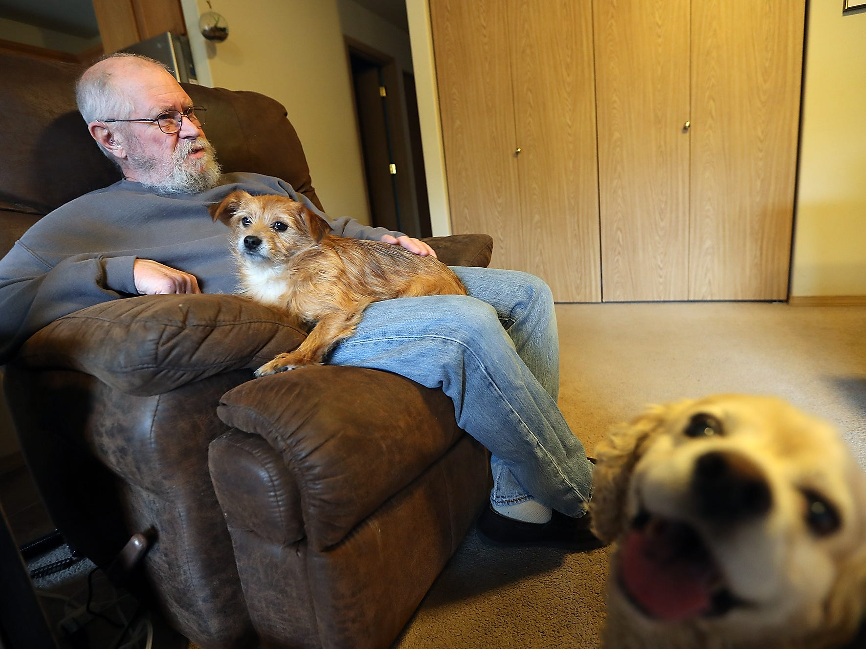John O'Connor and dog Spanky sit in John's chair as Ladybug photobombs in the foreground at their Port Orchard home on Thursday, December 20, 2018.