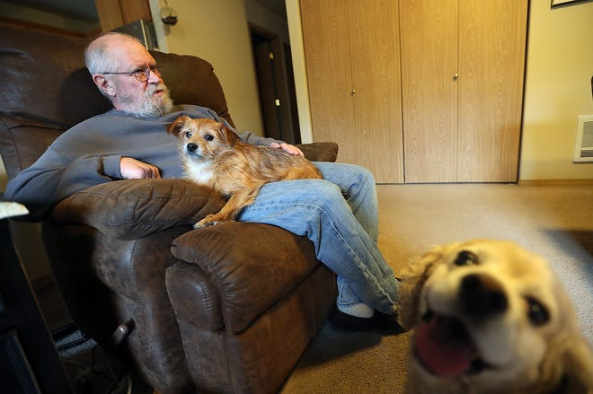 John O'Connor and dog Spanky sit in John's chair as Ladybug photobombs in the foreground at their Port Orchard home on Thursday.