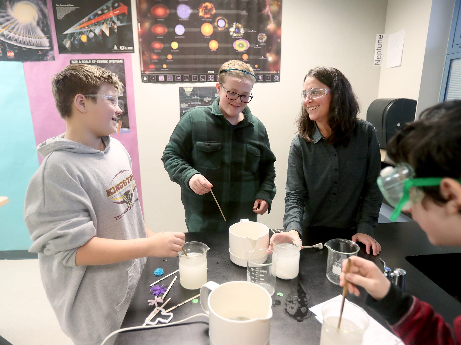 Karla Manuguid, top right, a science teacher at  Kingston Middle School works with students on making a snowflake, in class.