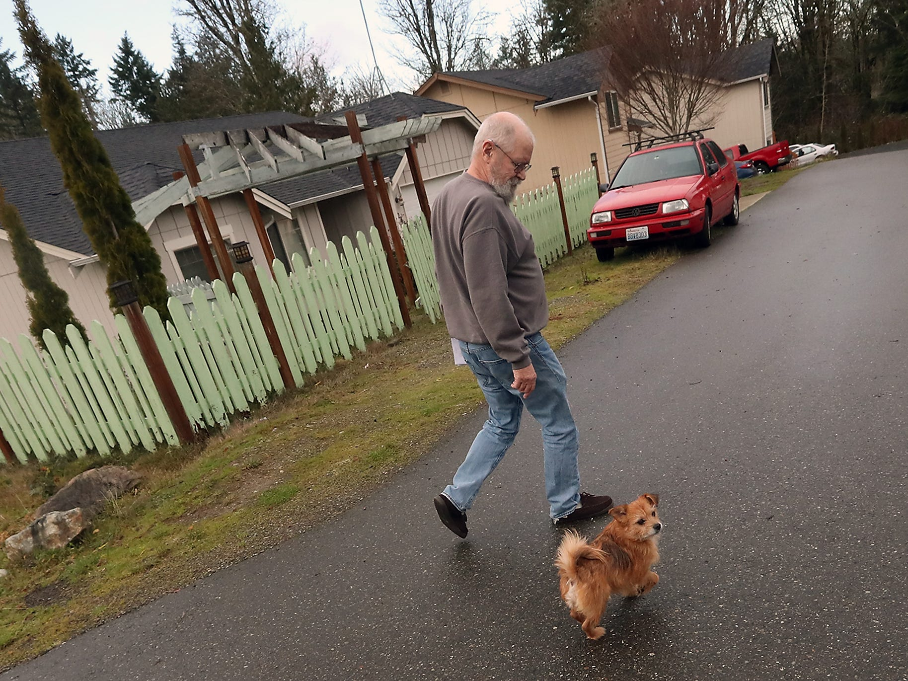John O'Connor's dog Spanky walks next to him as they head back to  he house after getting their mail at their Port Orchard home on Thursday, December 20, 2018.