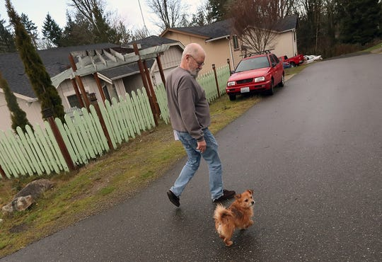 John O'Connor's dog Spanky walks next to him as they head back to yhe house after getting their mail at their Port Orchard home on Thursday.