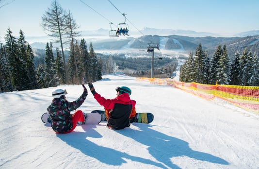 Snowboarders Sit On The Top Of The Ski Slope Under The Ski Lift Let S High Five To Each Other With A Beautiful Scenery Of Mountains And Forests On A Sunny Morning