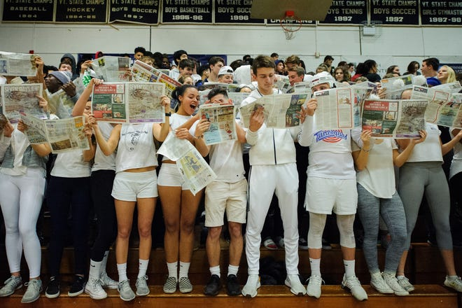 Burlington fans hold up newspapers during the player introductions for Rice during the boys basketball game between the Rice Green knight and the Burlington Sea Horses at Burlington High School on Thursday night December 20, 2018 in Burlington.