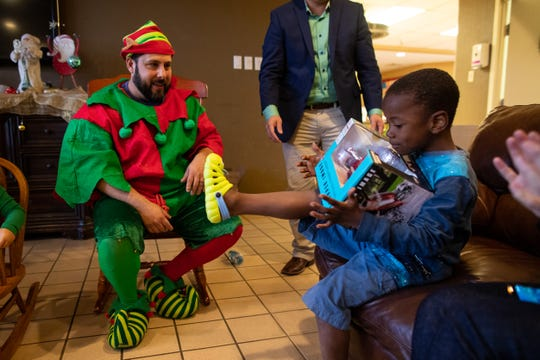 Steve Trevino, a comedian who grew up in Portland TX, hands out presents to patients staying at the the Ronald McDonald House of Corpus Christi on Friday, Dec. 21, 2018.