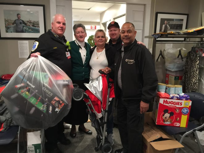 Sister Helen Cole (second from left) and Cooper University Hospital EMS personnel show some of the toys, clothes and other items they delivered Friday to families impacted by a North Camden rowhouse fire.