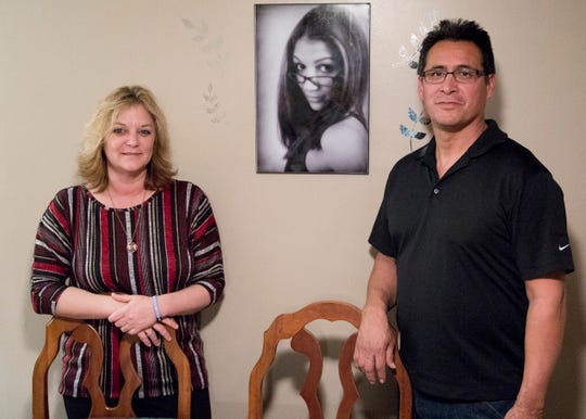 "Christina Arredondo and her husband Adam Arredondo pose in front of a picture placed in the dining room for all to see of their daughter Felicia ""Bugg"" Detty, who passed away from an overdose in 2015. The Arredondos hope the house will be the first of many, with each home being named after someone lost form an overdose."