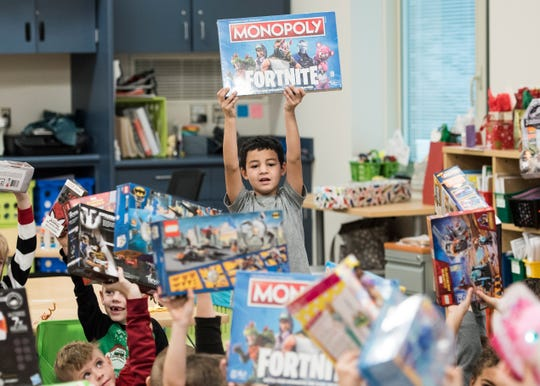 Chillicothe Primary School first grader Cameron Lett holds up his Monopoly Fortnite game as he and his fellow classmates open the gifts they received Friday morning. The students wrote Santa Claus a letter telling them what they wanted for Christmas, which was given to Thomas Worthington High School teacher Judith Galasso.