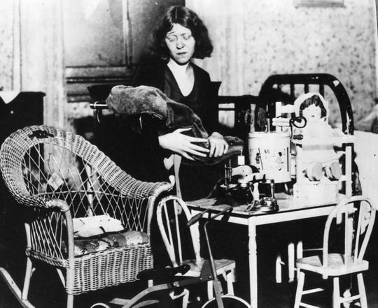 Mildred McLean poses with her daughter's toys after she went missing in 1931.