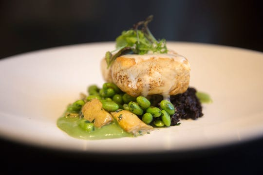 Halibut with artichoke, black rice, edamame, with sorrel cream. Chad Monk, The Mercer's chef de cuisine, prepares a main dish of halibut with artichoke, black rice, edamame, with sorrel cream. The dish is $36.00.