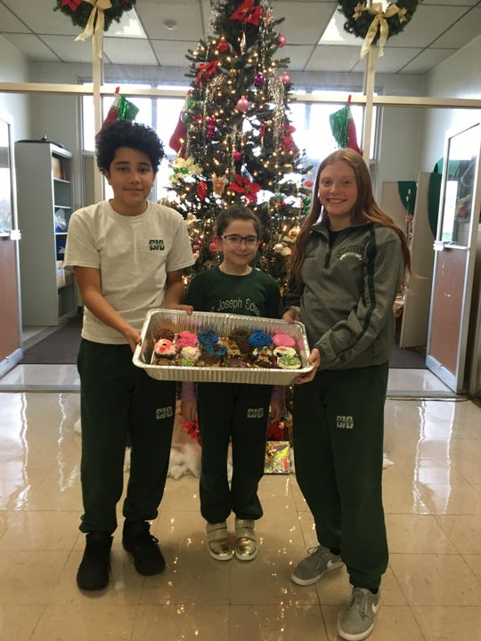 The National Junior Honor Society of St. Joseph School, Carteret, held a bake sale and raised $240 to contribute to the Building Fund of St. Mary's Ukrainian Catholic Church, which was ravaged by a fire on Nov. 27. Pictured looking over some of the cupcakes for sale are Michael-Tristan Almonte, NJHS vice president (left), Makayla Dean, president (right) and Camilla Yurchyshyn a parishioner at St. Mary's.