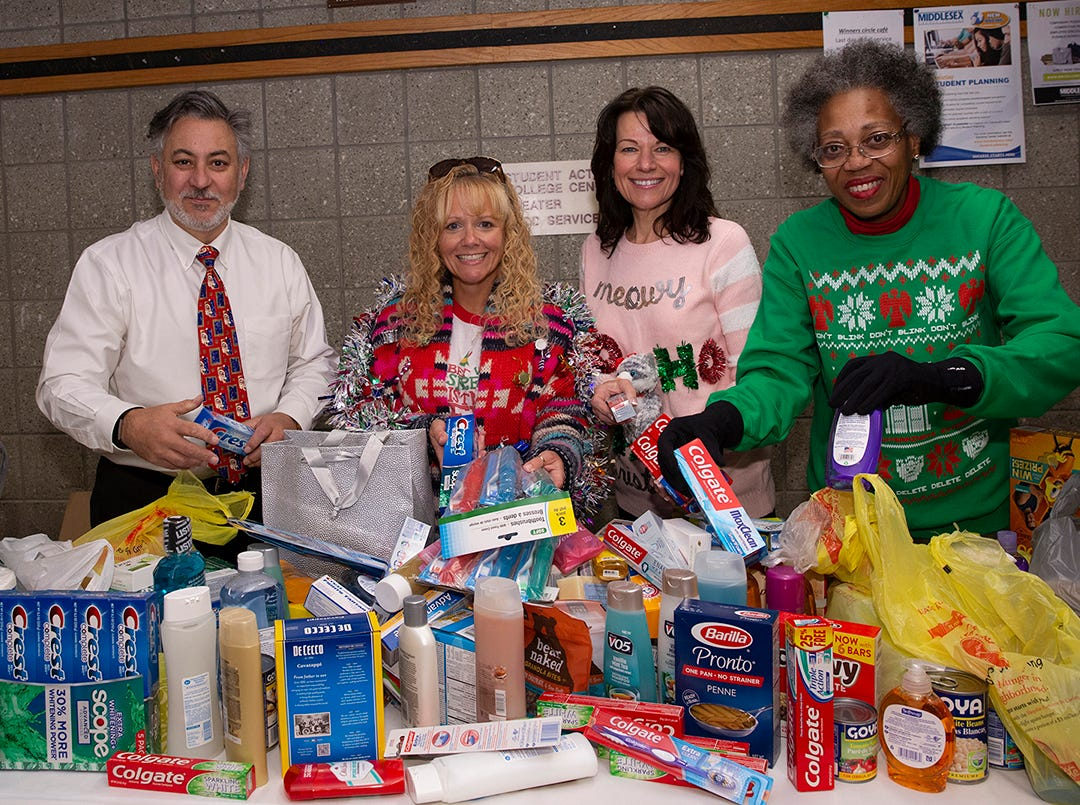 The Middlesex County College annual holiday party included an ugly sweater contest, karaoke, music, games, and a food drive that collected numerous boxes of food and personal hygiene items that were donated to the College's food pantry for students. Members of the College community dropped off food and supplies as they entered the party. From left, Joseph Nesi of Metuchen, accounting professor; Tracey Esser of Milltown, English Department assistant; Barbara Gillen of South Plainfield, admissions assistant; and Runae Wilson of Sayreville, psychology professor.
